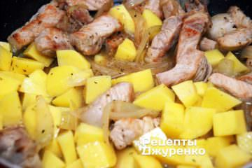 Очищенный картофель нарезать кубиками среднего размера и добавить к свинине