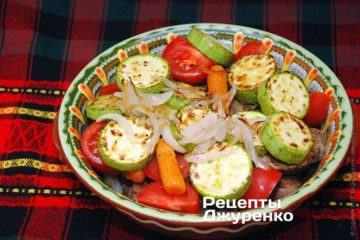 Поверх м'яса і цибулі викласти половину обсмаженої цибулі, морквини і кабачка