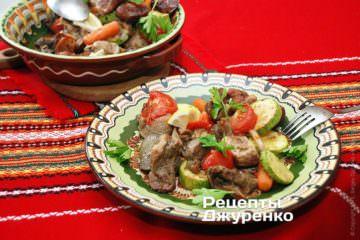 Поверх свинины с овощами разложить веточки петрушки и нарезанного крупными дольками лимона