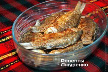 Вформу, смазанную сливочным маслом, выложить обжаренных карасей