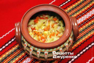 Поверх картошки выложит половину обжаренных овощей