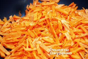 У розігріту олію викласти натерту моркву і обсмажувати її