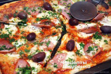 Посипати піцу зеленню і розрізати