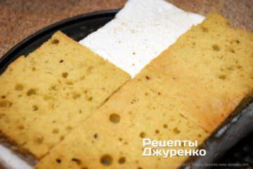 Поверх крема, выложить верхнюю часть кусков бисквита