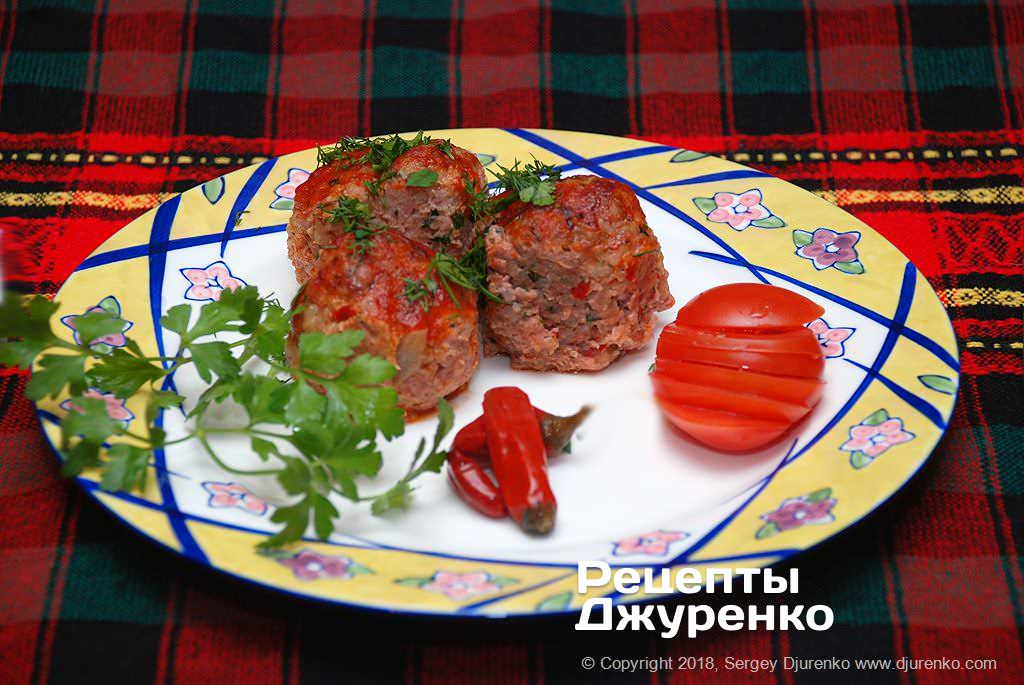 Готова страва Тефтелі з рисом в томатному соусі з перцем і зеленню.