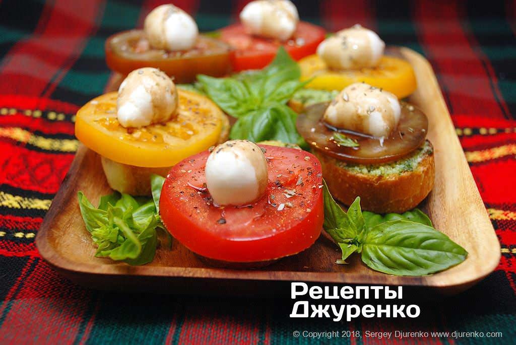 Готова страва Помідори з моцарелою і базиліком на скибочках підсмаженого хліба.