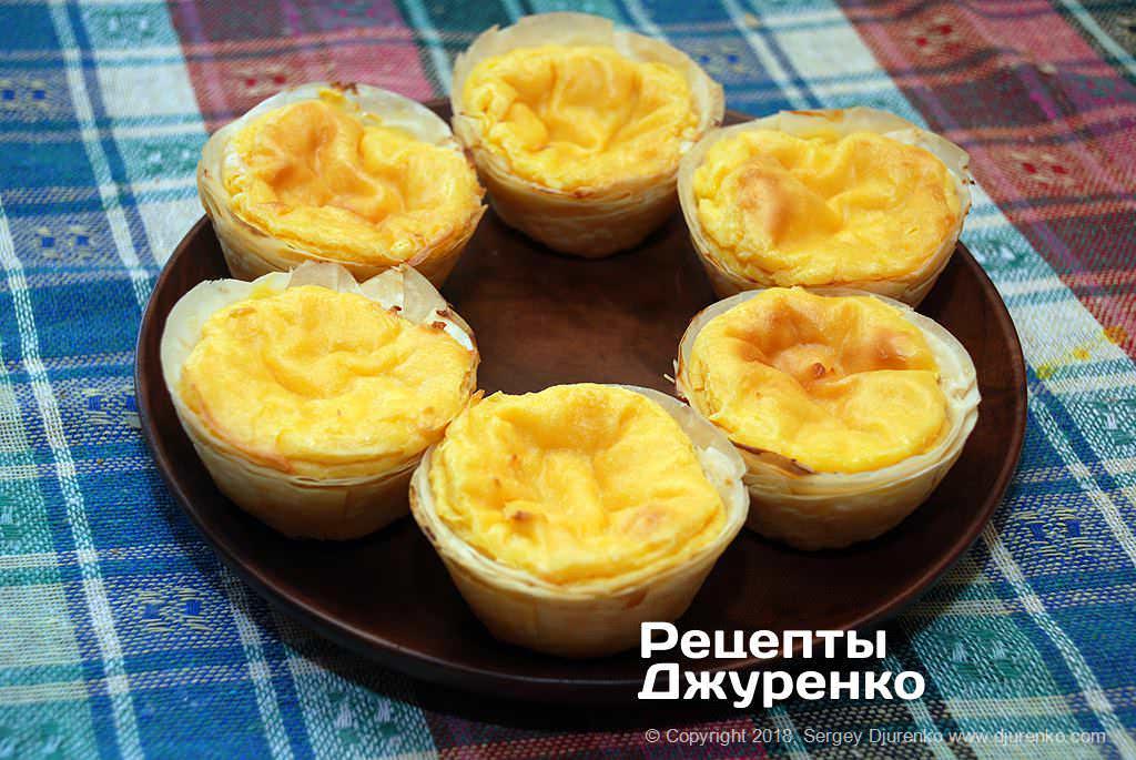 Яичные тарталетки из слоеного теста с запеченным заварным кремом.