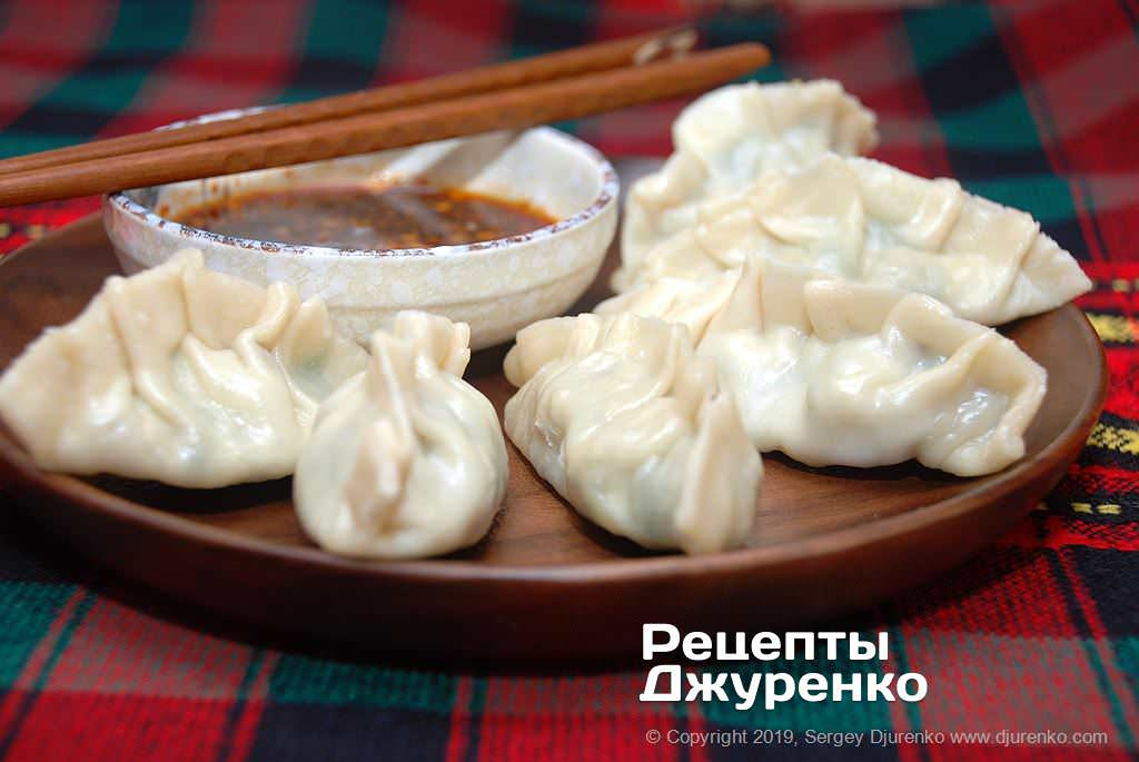 Готова страва Цзяоцзи - китайські пельмені особливої форми з пряним соусом.