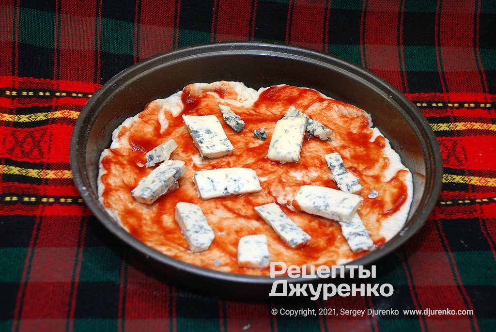 Змастити тісто томатом і розкласти сир.