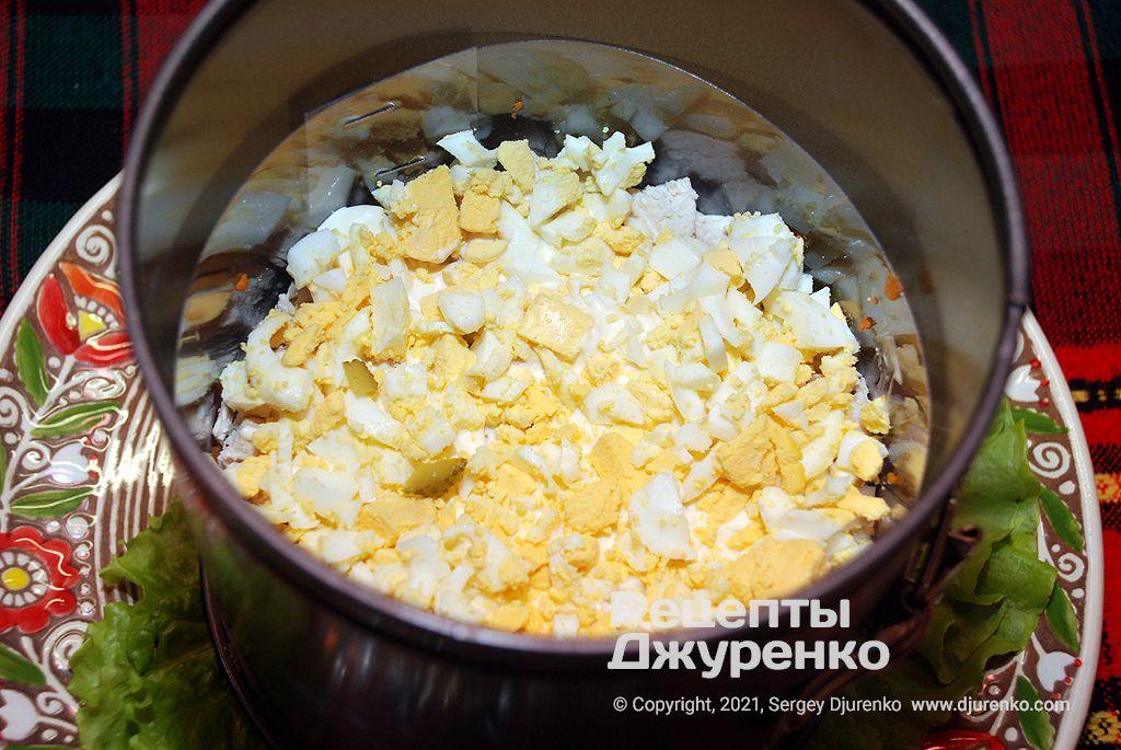 Разложить кусочки куриного филе и нарубленные яйца.