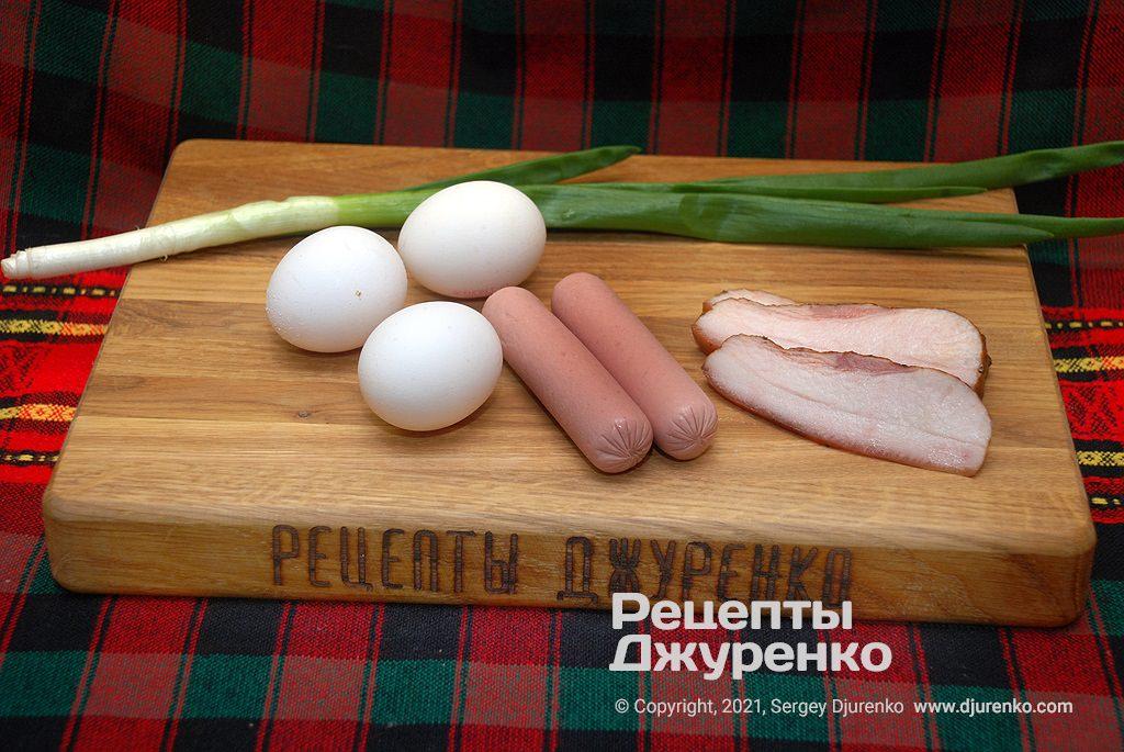 Свежие яйца, свиные сосиски, ломтики сала и немного зелени.