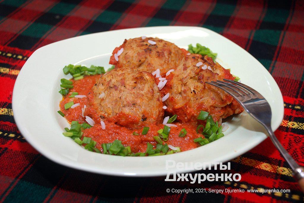 Готова страва Їжачки в духовці - запечені м'ясні кульки зі свинини та рису.