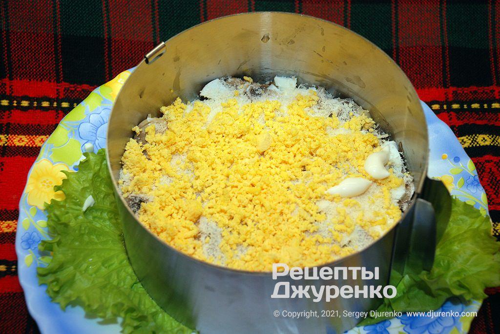 Посипати салат жовтками.
