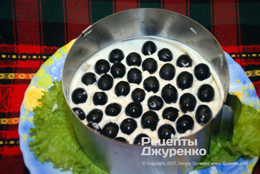 Змастити верх майонезом і укласти половинки чорних оливок.