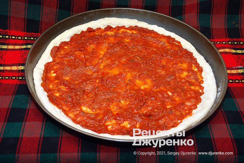 Обильно смазать тесто готовым томатным соусом.