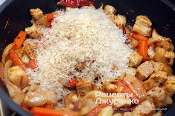 Всыпать рис и недолго жарить его вместе с мясом и овощами.