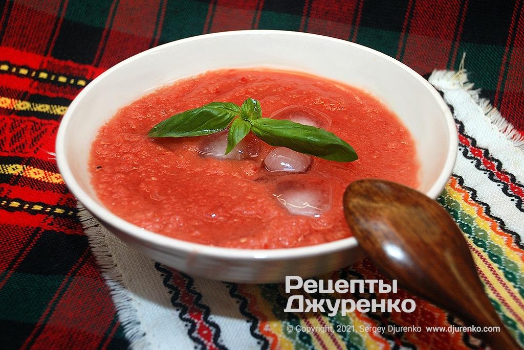 Готова страва Літній суп з стиглих томатів, овочів і з кубиками льоду.