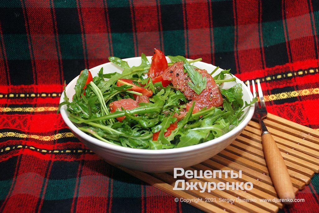 Салат с рукколой, томатами, зеленью и ломтиками грейпфрута.