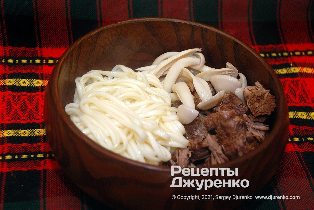 Викласти в тарілку локшину, яловичину і гриби, потім залити томатним бульйоном.