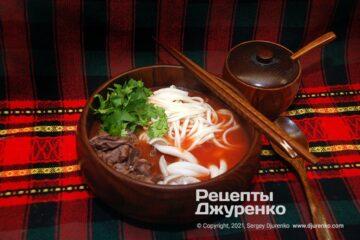 Готова страва Томатний суп з яловичиною та локшиною, грибами і зеленню.