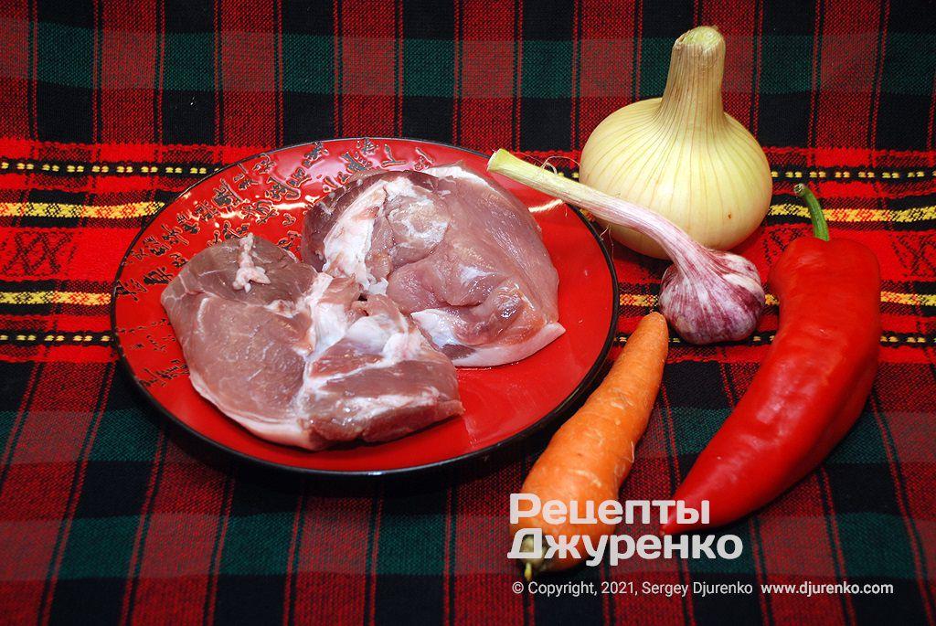Шматки свинини і овочі для печені.