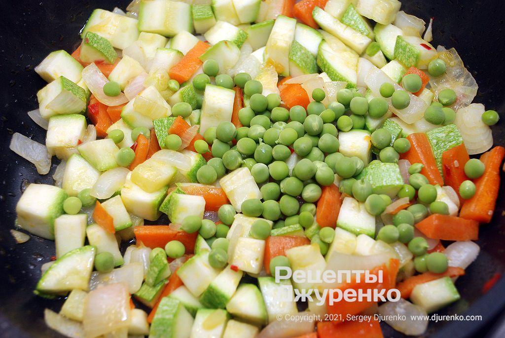 Добавить к овощам кабачок и зеленый горошек.
