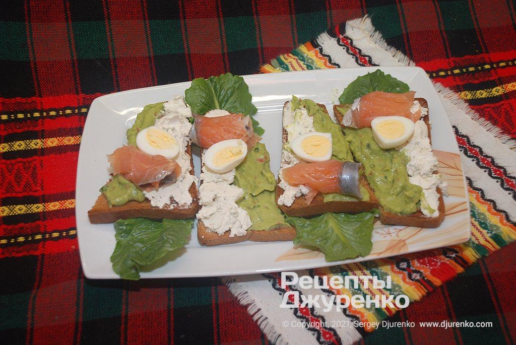 Смазать хлеб крем-сыром и соусом, затем добавить малосольную рыбу.