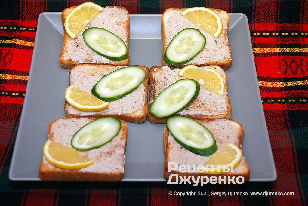 Змастити підсмажений хліб крем-сиром і розкласти скибочки огірка і лимона.