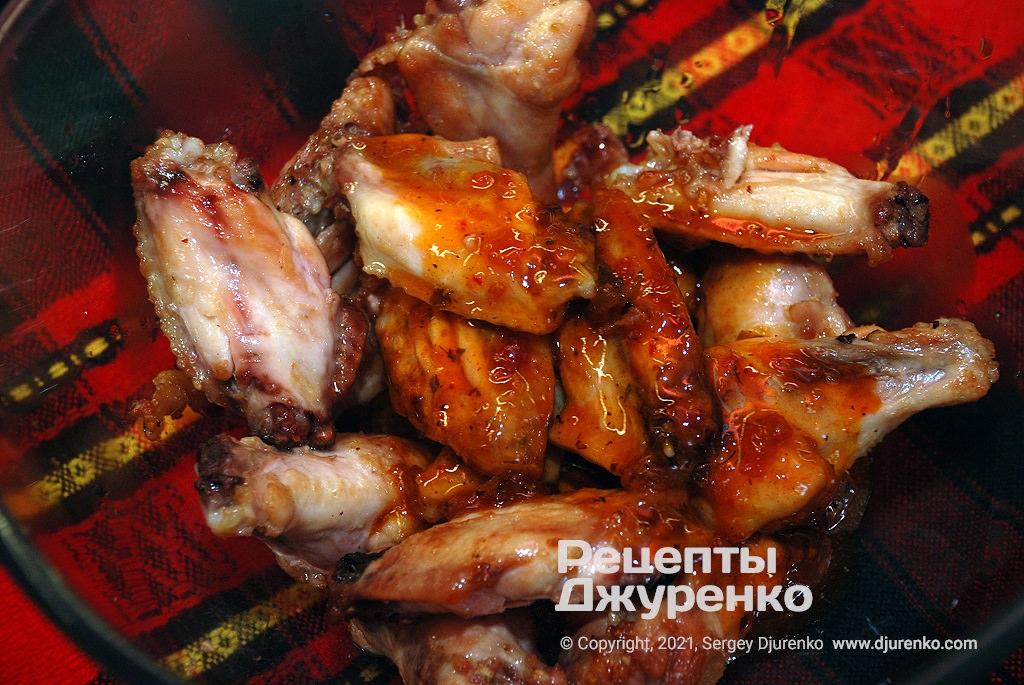 Покрити шматочки крил соусом і поставити ще раз в духовку.