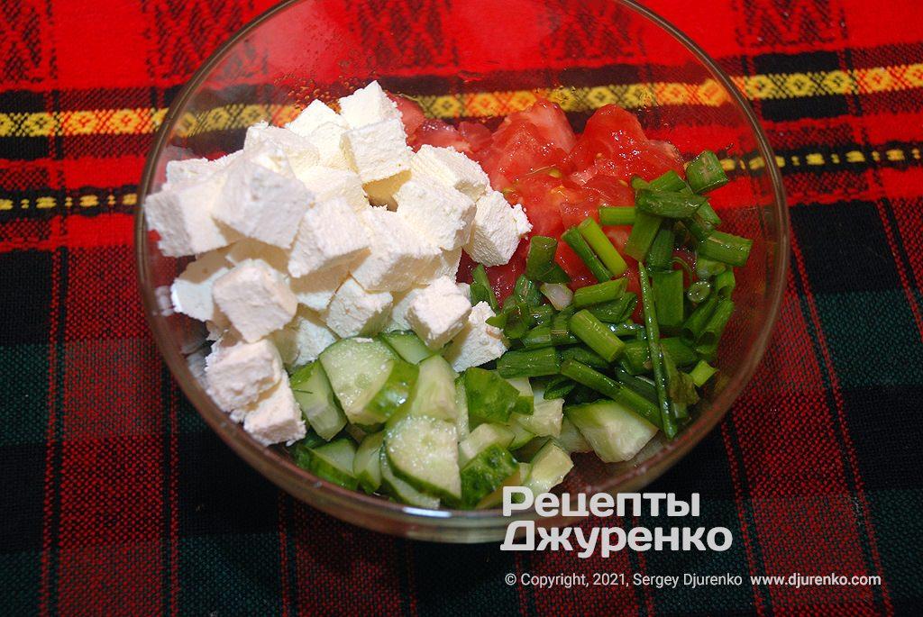 Нарізати огірки, м'якоть помідорів, бринзу і перо зеленої цибулі.