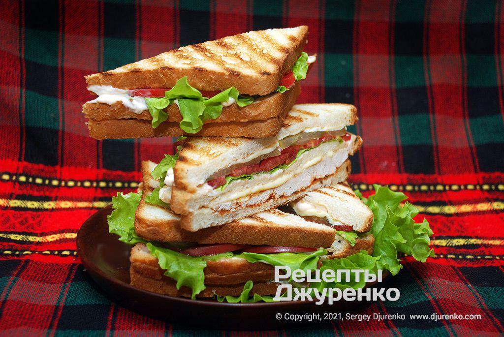 Сэндвич с курицей на ломтиках хлеба с соусами и овощами.